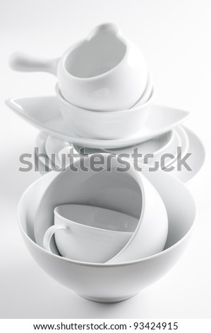 A lot of white crockery and kitchen utensils on white background
