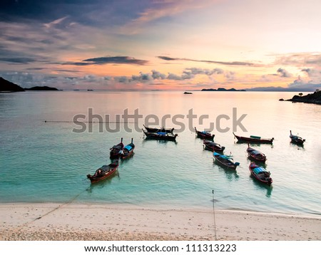 A lot of wooden boats near the beach at sunrise. View from above