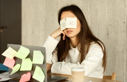 A lot of work concept. Tired freelancer sleeping at workplace with stickers on eyes