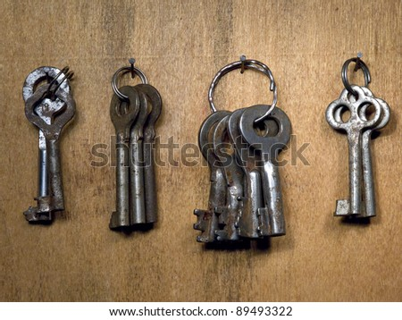 A lot rusty old keys on a wooden wall.
