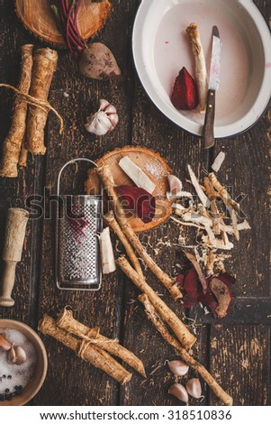 A lots of horseradish root and beetroot with knife over on a cutting board on a old wooden table. Horseradish and beet roots for food which is a root of plant. Rustic dark style.