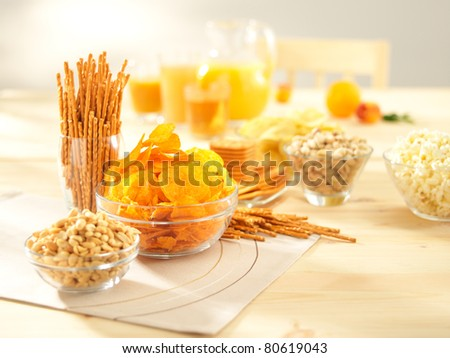 A lots of salty snacks with juice on a wooden table - stock photo