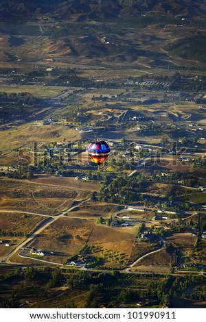 A love hot air balloon rises over the landscape