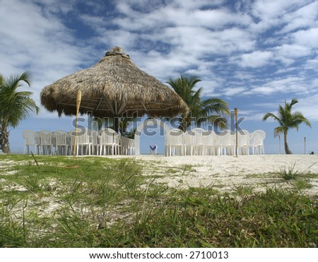 A lovely beach wedding site under a rustic tiki cabana and on a scenic outcrop
