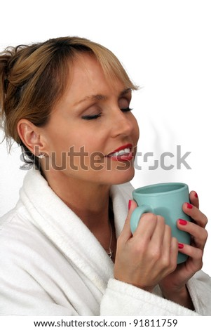 A lovely blonde with a captivating smile and wearing a white bathrobe, enjoys a hot beverage.  Isolated on a white background.