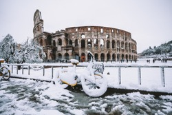 A lovely day of snow in Rome, Italy, 26th February 2018: a view of snowy bikes behind the Colosseum