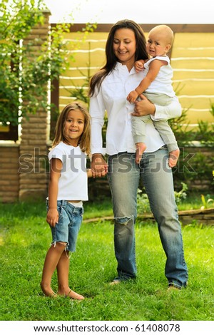 A lovely mother and her daughter standing in front of their home on a sunny, summer day. - stock photo