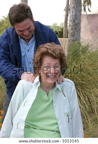 A lovely senior woman enjoying a back massage in the garden. - stock photo