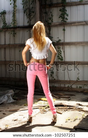 A lovely strawberry-blonde woman stands facing away from the camera wearing pink jeans in a long-abandoned warehouse facility.