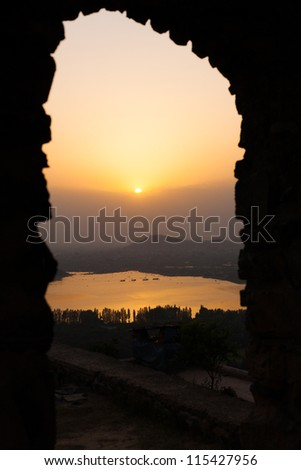 A lovely sunset is seen through a framed silhouette gateway over Dal Lake and the fort in the distance in Srinagar, Kashmir, India