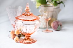A lovely vintage pink candy dish from the depression era surrounded by additional vintage pieces on a light, clean background.