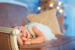 A lovely 3 year old girl in a beautiful white dress lying on a sofa in front of the decorated Christmas tree