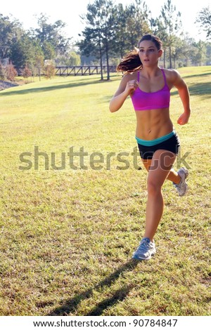 A lovely young athlete with remarkable abdominal musculature jogging outdoors.  Generous copyspace.