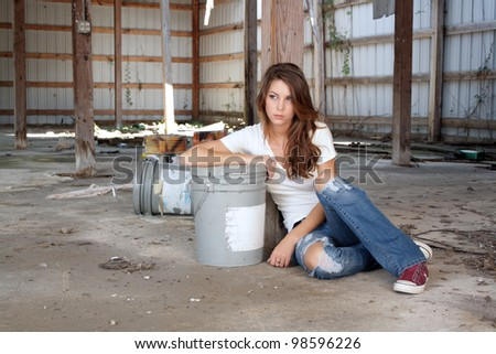 A lovely young brunette in dress-down casual wear sits on the floor of a long-abandoned warehouse.