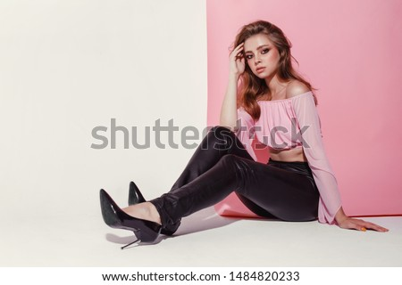 A lovely young female with professional make-up sits like a doll with long legs on a pink white background in a short top and leather leggings, copyspase