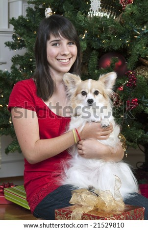 A lovely young girl in front of a Christmas tree holding her little dog.