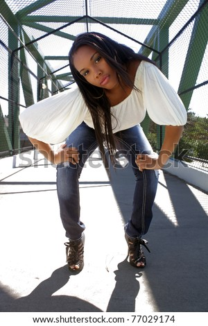A lovely young Haitian girl on a pedestrian overpass covered with chain-link fence, bends over toward the low-angle camera.