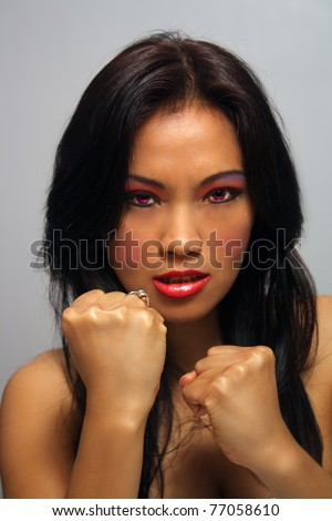 A lovely young Indonesian model with long, luscious black hair holds her fists up ready to fight.  Her glowing red eyes match her fiery persona.