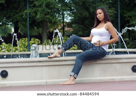 A lovely young multiracial woman, five months pregnant, sits on the edge of an outdoor water fountain.