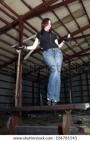 A lovely young redhead wearing jeans and chains, stands in an abandoned warehouse facility.