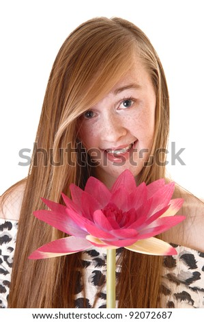 A lovely young teenage girl in a portrait picture with a pink water lily, smiling into the camera, with long hair for white background.