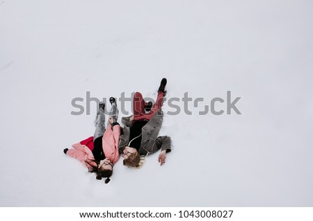 a loving couple - a girl in a pink coat and glasses and a guy in a gray coat and pink pants and glasses are lying on the snow, a mountain winter landscape #1043008027