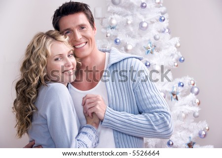 A loving couple in front of the christmas tree