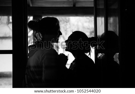 a loving couple in turtle and skeleton pajamas hugs in  wooden house, in front of window,  black and white photo #1052544020