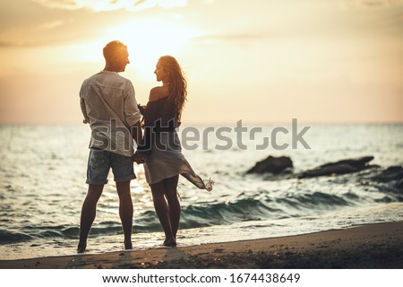 A loving couple is having fun and hugging on the empty sandy sea beach at sunset.They are looking each other and happily smiling. Stockfoto ©