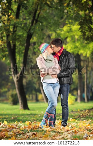 A loving couple kissing in the park in autumn
