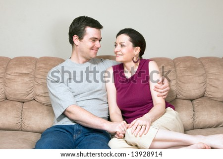 A loving couple looking at each other smiling and sitting on a sofa.  The man has his arm around the woman. - stock photo