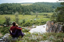 A loving couple sits on a rock. a man and a woman hug each other. seclusion. love. Nature of Russia