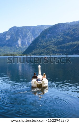 A loving couple swims in a boat in the form of a swan on a lake in the Austrian Hallstatt. Picturesque landscape on a warm autumn day. Honeymoon. Honeymoon trip #1522943270