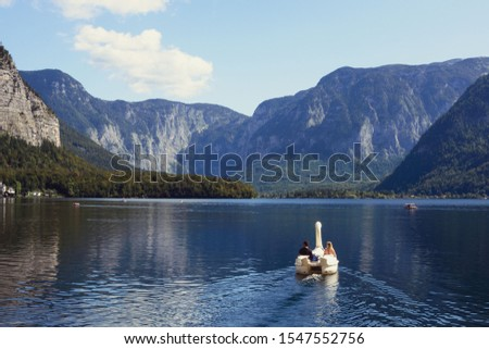 A loving couple swims in a boat in the form of a swan on a lake in the Austrian Hallstatt. Picturesque landscape on a warm autumn day. Honeymoon. Honeymoon trip #1547552756