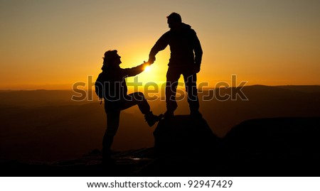 A loving couple walking holding hands Silhouetted by the sunset