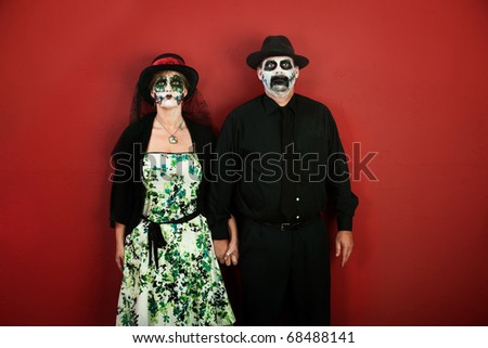 A loving middle-aged couple wearing make up for Halloween or All Souls Day