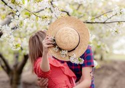 A loving young couple kissing, covering themselves with a hat. Love in the cherry blossom garden