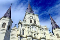 A low, abstract angle of Saint Louis Cathedral on Jackson Square in the New Orleans French Quarter with a dramatic blue sky with white clouds.