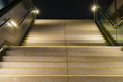 A low angle closeup of stairs with yellow lining and metallic rails with lights at night