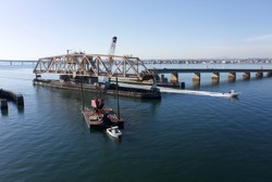 A low angle drone shot of a swing bridge that is opened to allow a tall dredge to pass. It is a sunny say in the afternoon and the skies are blue. The water of the bay is calm.