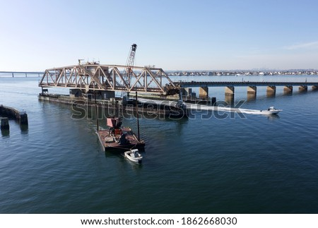 A low angle drone shot of a swing bridge that is opened to allow a tall dredge to pass. It is a sunny say in the afternoon and the skies are blue. The water of the bay is calm. Foto stock ©