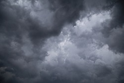 A low angle greyscale of a dark cloudy sky in the evening - perfect for backgrounds and wallpapers