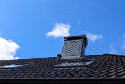 A low angle of the black clay tile roof of a house under the cloudy blue sky