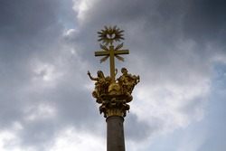 A low-angle shot of a golden Christian cross with a halo above and sculptures of angels on a cloudy sky