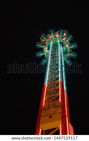 A low angle shot of a tower attraction at a park during the night