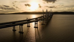 A low angle shot of the Governor Mario M. Cuomo Bridge, also known as the Tappan Zee Bridge. The bridge crosses over the Hudson River and was shot during a cloudy & golden sunset.