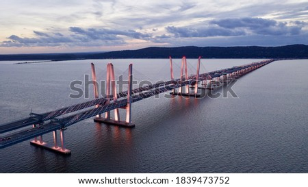 A low angle shot of the Governor Mario M. Cuomo Bridge, also known as the Tappan Zee Bridge. The artfully designed bridge over the Hudson River was illuminated in pink during a cloudy sunset. Stockfoto ©