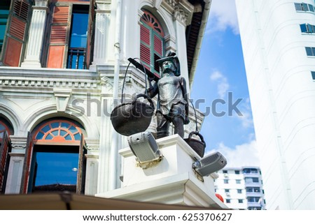A low angle view of a Chinese laborer stature in the mid of China town, symbol of the origin of the town. Singapore.
