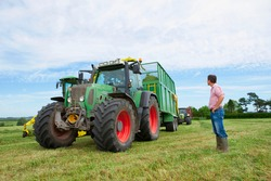 A low angle view of a Farmer looking up at the tractor and trolley collecting the freshly cut hay in a vast farm field