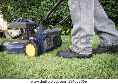 A low angle view of a man preparing for lawn mowing